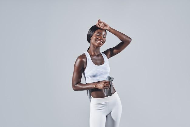 Glückliche junge afrikanerin in sportkleidung, die eine flasche mit wasser hält und die stirn berührt