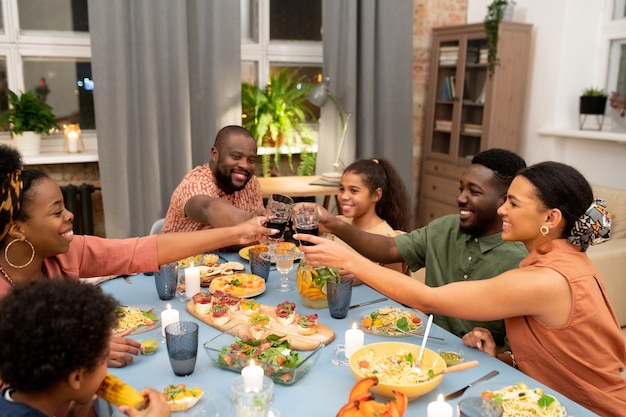 Glückliche junge afrikanerin, mann, teenager und mädchen, die mit hausgemachtem rotwein am festlichen tisch klirren, serviert mit hausgemachtem essen