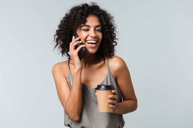 Glückliche junge afrikanische frau beiläufig gekleidet stehend isoliert, auf handy sprechend, tasse zum mitnehmen haltend kaffee