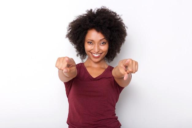 Glückliche junge afrikanische frau, die beide hände zeigt und auf weißem hintergrund lächelt