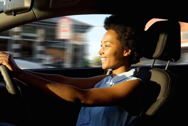 Glückliche junge afrikanische frau, die ein auto antreibt