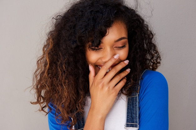 Glückliche junge afrikanische frau, die gegen graue wand kichert