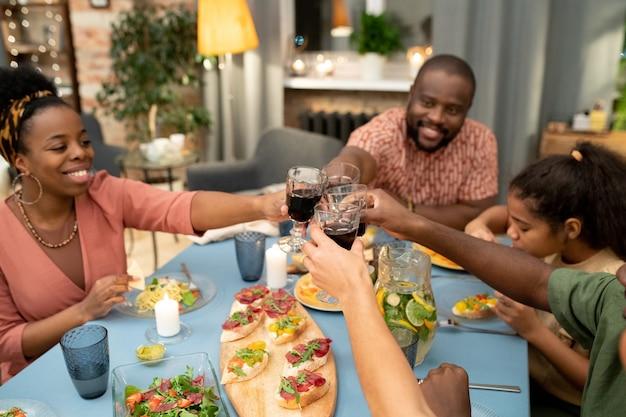 Glückliche junge afrikanische frau, ihr ehemann, sohn und tochter im teenageralter klirren mit gläsern gefüllt mit hausgemachtem rotwein am festlichen tisch