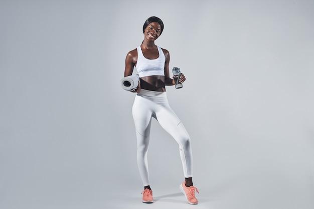 Glückliche junge afrikanische frau in sportkleidung, die flasche mit wasser und gymnastikmatte hält