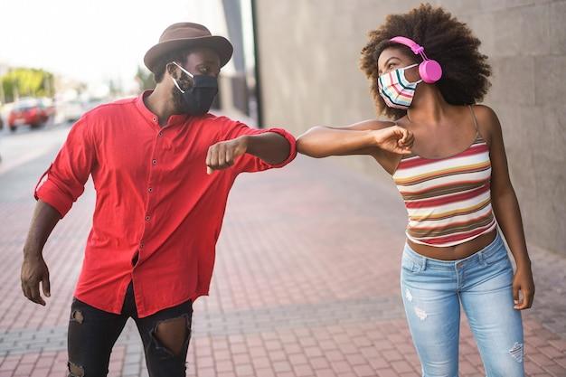 Glückliche junge afrikanische freunde, die ihre ellbogen stoßen, anstatt mit einer umarmung zu grüßen - konzentrieren sie sich auf frauenaugen