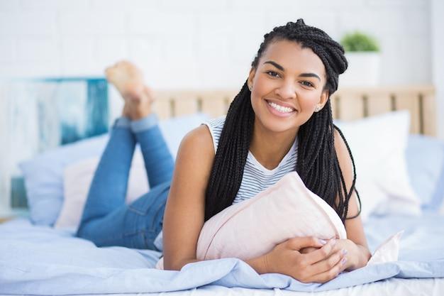 Glückliche junge afro-amerikanische frau ruht im bett