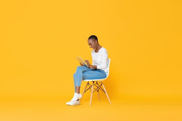 Glückliche junge afroamerikanerfrau, die auf einem stuhl unter verwendung des tablet-computers sitzt