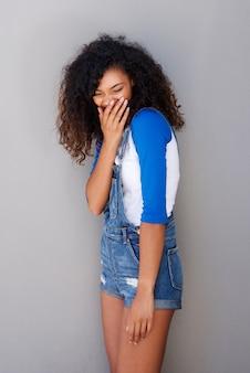 Glückliche junge afroamerikanerfrau, die gegen graue wand kichert