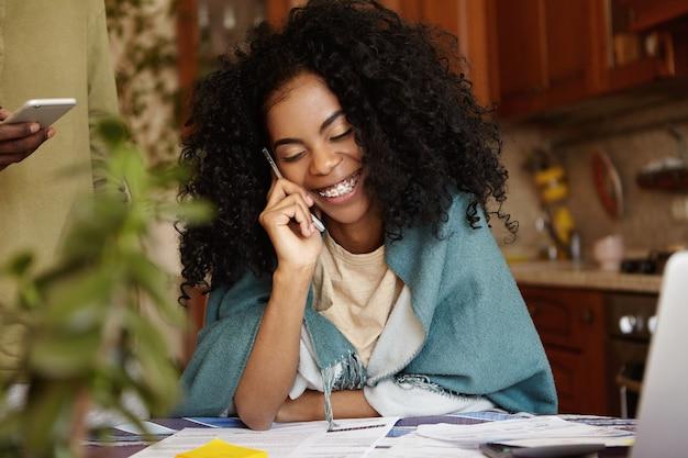 Glückliche junge afroamerikanische hausfrau, die wrap trägt, die telefongespräch genießt