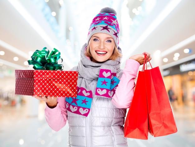 Glückliche junge amerikanische frau mit einem weihnachtsgeschenk in einer winteroberbekleidung