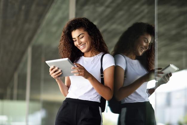 Glückliche junge arabische frau, die digitale tablette im geschäftshintergrund verwendet.
