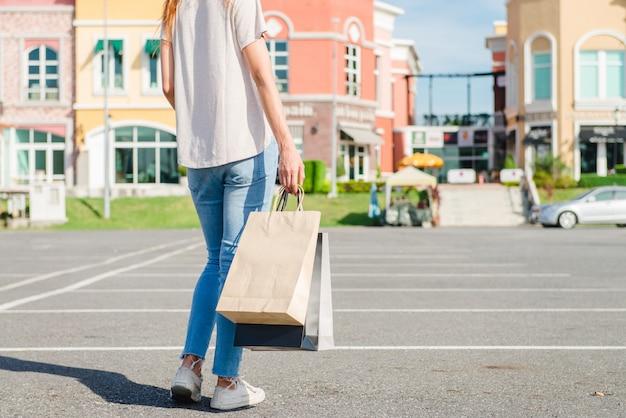Glückliche junge asiatin, die einen markt im freien mit einem hintergrund von pastellgebäuden kauft