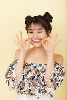 Glückliche junge asiatin, die im studio mit offenem lächeln und lustigen handzeichen aufwirft