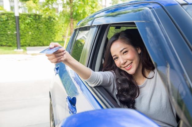 Glückliche junge asiatin, die zahlungskarte oder kreditkarte hält und verwendet wird, um für benzin, diesel und andere brennstoffe an den tankstellen zu zahlen
