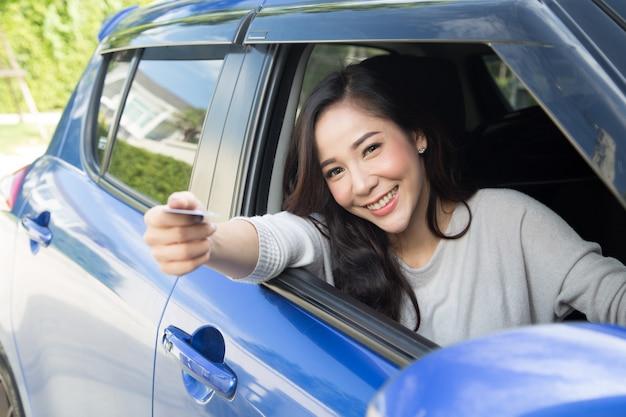Glückliche junge asiatin, die zahlungskarte oder kreditkarte hält