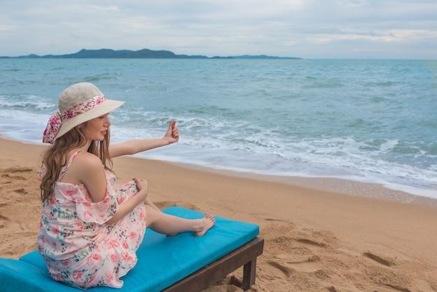 Glückliche junge asiatin mit dem hut, der auf strandstuhl sich entspannt und fingerherz tut.