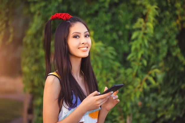 Glückliche junge asiatin mit dem smartphone, der in der straße steht