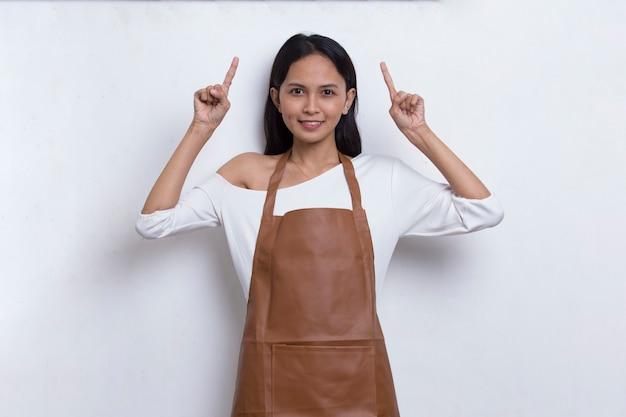 Glückliche junge asiatische barista-kellnerin, die mit den fingern in verschiedene richtungen zeigt