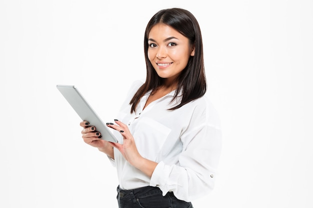 Glückliche junge asiatische dame, die durch tablet-computer chattet