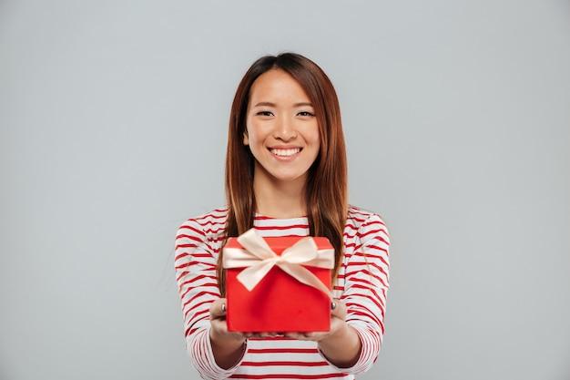 Glückliche junge asiatische dame, die geschenk hält.