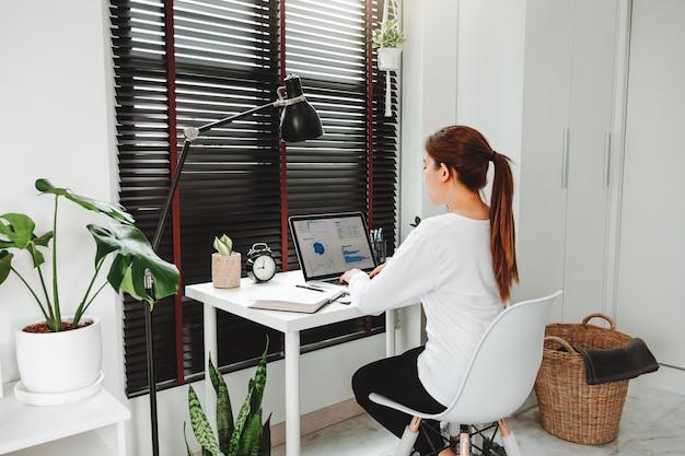 Glückliche junge asiatische frau arbeiten von zu hause aus und arbeiten an einem sozialen laptop-netzwerk