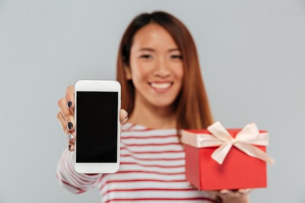 Glückliche junge asiatische frau, die anzeige des telefonhalteschenks zeigt.