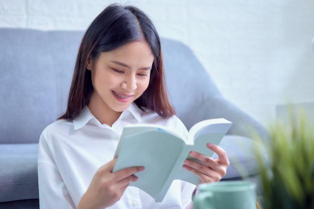 Glückliche junge asiatische frau, die auf sofa sitzt und buch in ihrem wohnzimmer, ferienzeit liest.