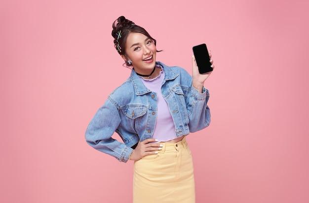 Glückliche junge asiatische frau, die bei leerem bildschirmhandy und handgestenerfolg lokalisiert über rosa hintergrund zeigt.