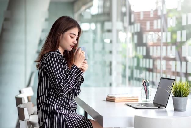 Glückliche junge asiatische frau, die kaffee am tisch mit laptop im café trinkt.