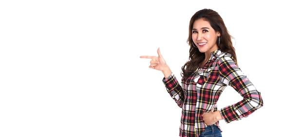 Glückliche junge asiatische frau, die mit ihrem finger lokalisiert über weißer wand mit kopienraum steht.
