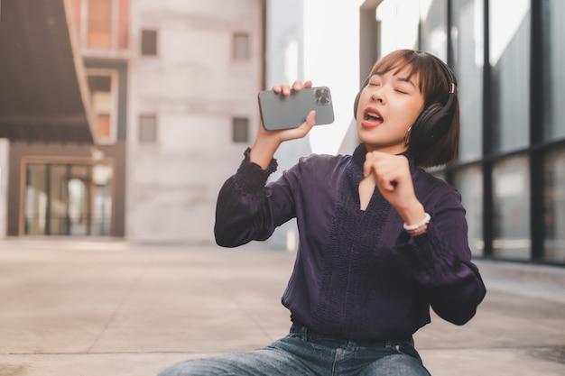 Glückliche junge asiatische frau, die musik mit kopfhörern über smartphone hört und spaß hat, während sie auf der straße sitzt.