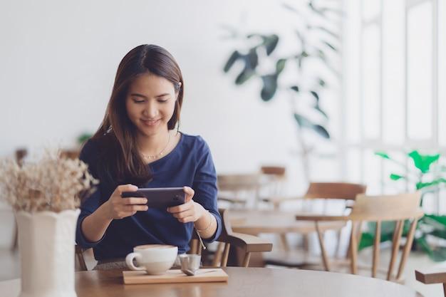 Glückliche junge asiatische frau, die smartphone mit lächelndem gesicht im kaffeecaféshop verwendet