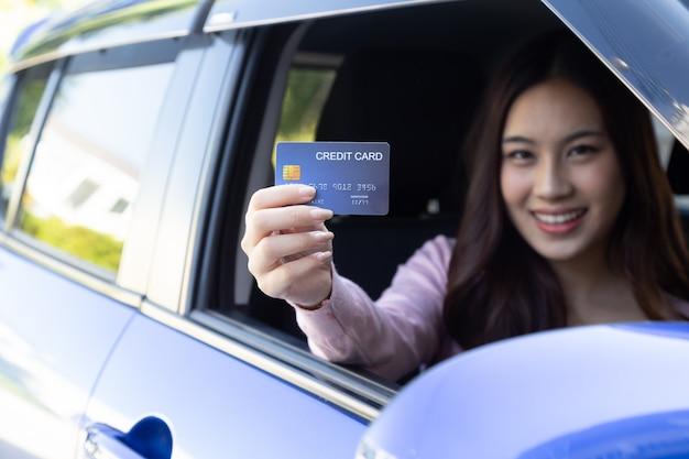 Glückliche junge asiatische frau, die zahlungskarte oder kreditkarte hält und verwendet, um für benzin, diesel und andere kraftstoffe an tankstellen zu bezahlen, fahrer mit flottenkarten zum auftanken des autos