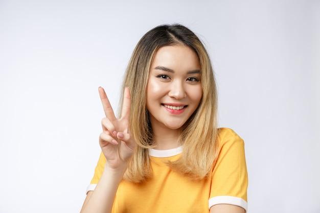 Glückliche junge asiatische frau, die zwei finger oder siegesgeste zeigt
