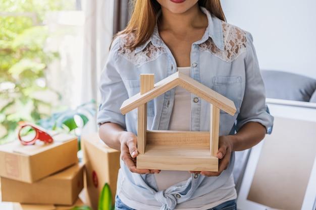 Glückliche junge asiatische frau im wohnzimmer am neuen haus mit stapel von pappkartons am umzugstag