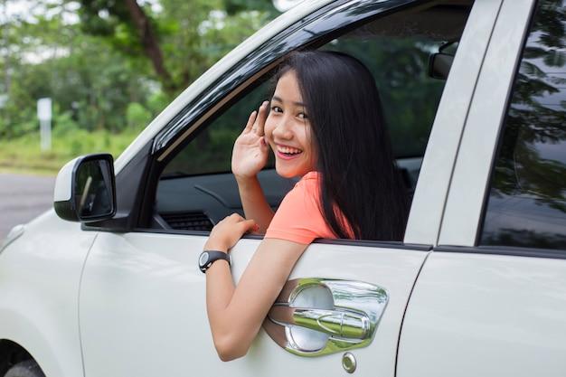 Glückliche junge asiatische frau lächelnd, während in ihrem auto sitzen