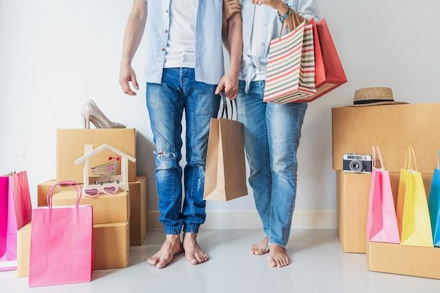 Glückliche junge asiatische frau mit bunter einkaufstasche, modeartikel und stapel von pappkartons zu hause