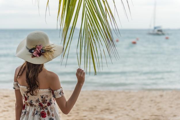 Glückliche junge asiatische frau mit dem hut, der auf strand sich entspannt