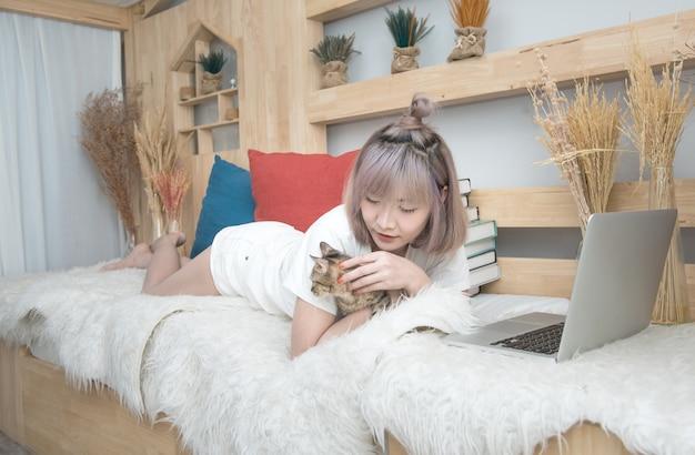 Glückliche junge asiatische frau mit laptop-computer-streichelkätzchen, das auf bett legt