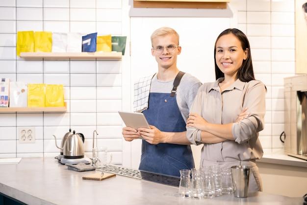 Glückliche junge asiatische frau und ihr männlicher kollege in der arbeitskleidung, die sie mit freundlichem lächeln während der arbeit betrachten