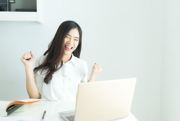 Glückliche junge asiatische geschäftsfrau beendete ihre arbeit.