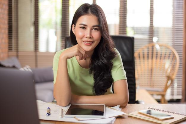Glückliche junge asiatische geschäftsfrau, die gerade in die kamera schaut, während sie sitzt und an ihrem projekt mit ihrem computer und tablet arbeitet
