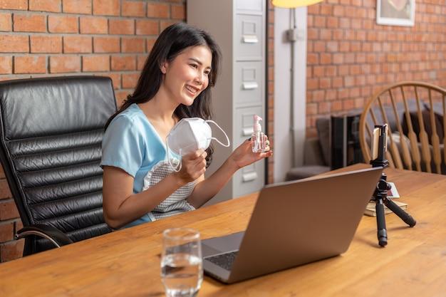 Glückliche junge asiatische geschäftsfrau, die n95 gesichtsmaske und alkoholsprühflasche hält, um ihre social-media-fanseite zu zeigen