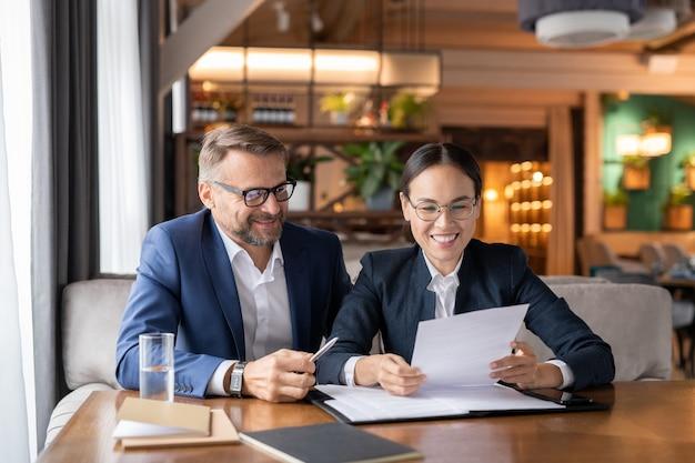 Glückliche junge asiatische geschäftsfrau, die vertragspunkte und bedingungen durchschaut, bevor sie es nach verhandlung mit partner unterschreibt