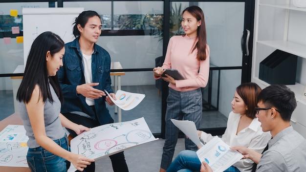 Glückliche junge asiatische geschäftsleute und geschäftsfrauen, die brainstorming-ideen treffen