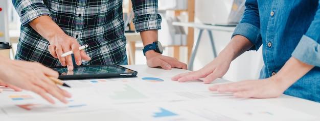 Glückliche junge asiatische geschäftsleute und geschäftsfrauen, die brainstorming-ideen über neue papierkramprojektkollegen treffen, die zusammenarbeiten, um erfolgsstrategie zu planen, genießen teamarbeit in einem kleinen modernen büro.