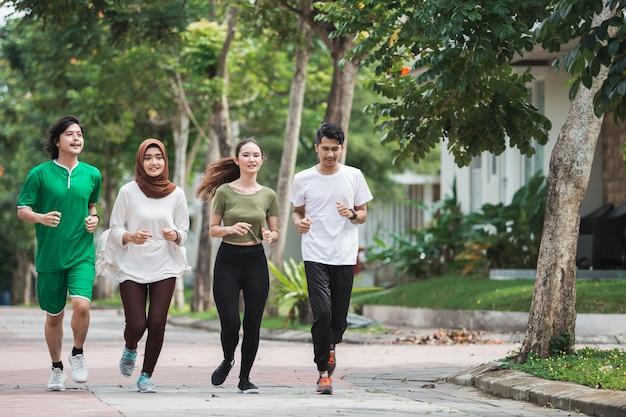 Glückliche junge asiatische leute trainieren und wärmen sich auf