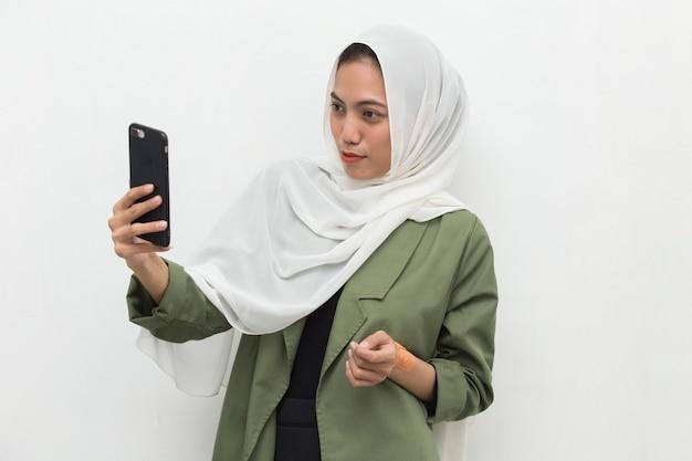 Glückliche junge asiatische muslimische frau, die handy verwendet