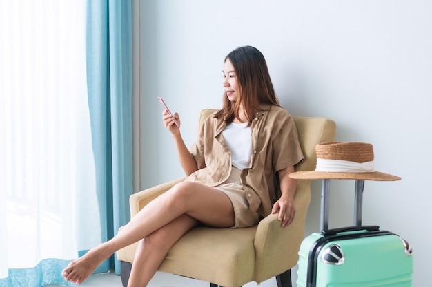 Glückliche junge asiatische reisende frau, die auf sofa sitzt, während smartphone verwendet, um ihre reise zu planen