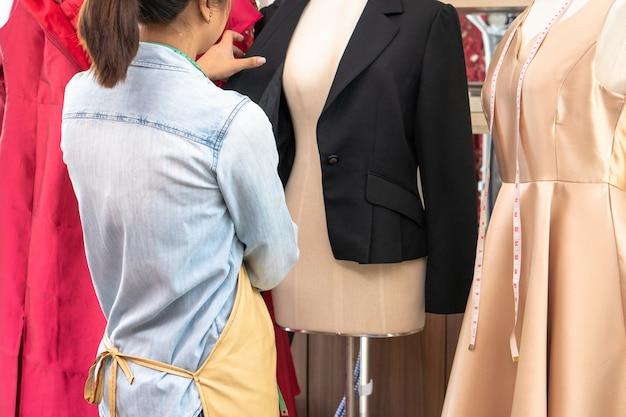 Glückliche junge asiatische schneiderin modedesignerin sucht nach fertigstellung für einen anzug und ein kleid in einem ausstellungsraum. erfolgskonzept jungunternehmer im modegeschäft.